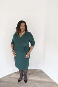 beautiful, smiling black woman with shoulder length hair wearing pearls and a green dress with her hands resting on her hips standing a bit in front of a white wall as though she was doing a presentation