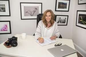 woman in a white camisole and whte and gray striped sweater with long brown hair and blue eyes smiling while sitting a white desk writing in a planner with a pair of glasses, a white coffee mug, a nikon camera and an apple mac book pro sitting on the desk