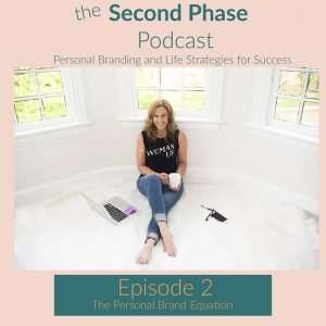 "the graphic for the second phase podcast is a pink square with a photo of Robyn Graham in a black tee that says ""Woman Up"" and a pair of distressed jeans. She is sitting on a white rug with a white coffee mug and her computer next to her."