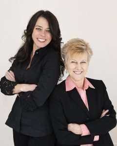 create a brand strategy session with mary fran bontempo and kristin smedley. both women are dressed in black and mary fran has a coral blouse u under her blazer. Kristin has long black hair and blue eyes and mary fran has short blond hair and blue eyes. both are smiling. kristin is standing and mary fran is sitting and the are leaning on each other with their arms crossed.