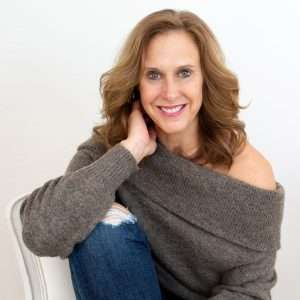 Robyn Graham is a brand marketing strategist, podcast host and photographer. In this image she is wearing a gray sweater with jeans and her right elbow is leaning on her right knee as she looks at the camera and smiles.
