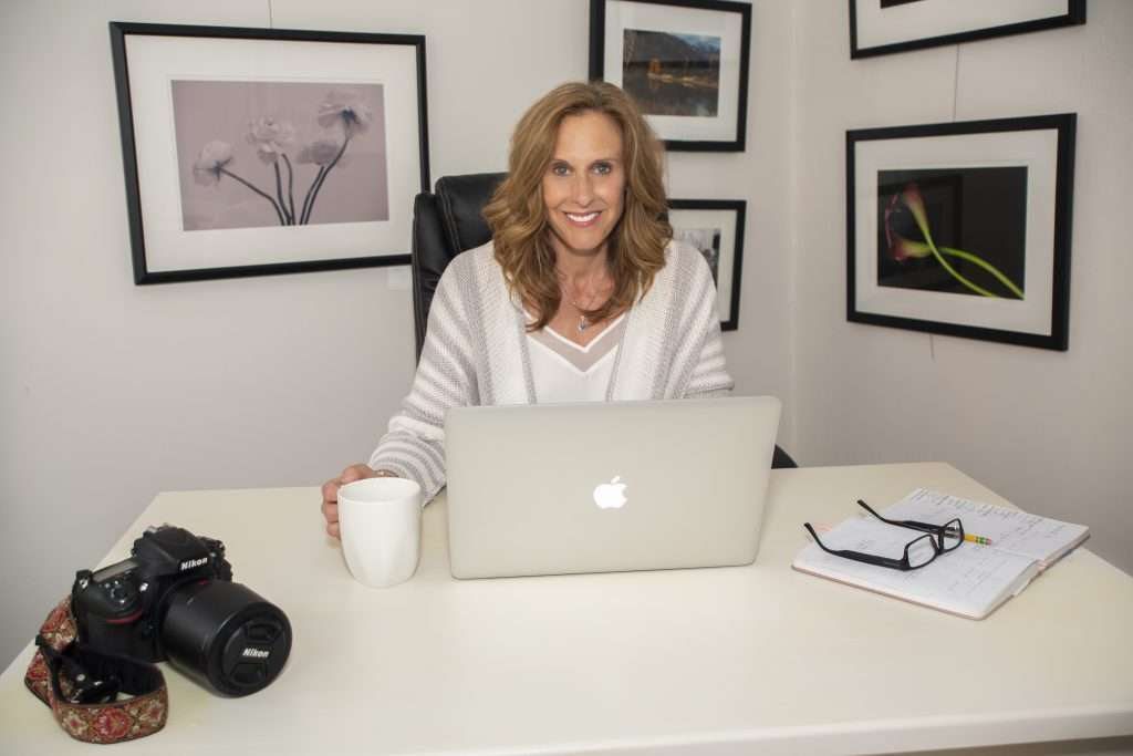 Robyn Graham is a brand marketing strategist, coach, podcast host and photographer. In this image she is sitting at a white desk with her mac in front of her and her camera on the corner of the desk looking at the camera and smiling.